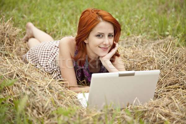 Young  fashion girl with notebook lying at field Stock photo © Massonforstock