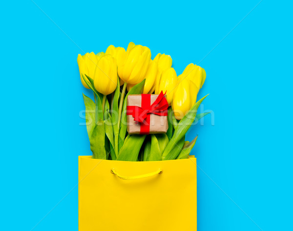 bunch of yellow tulips and cute gift  in cool shopping bag on th Stock photo © Massonforstock
