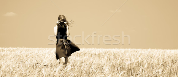 Girl at spring field with retro camera. Stock photo © Massonforstock