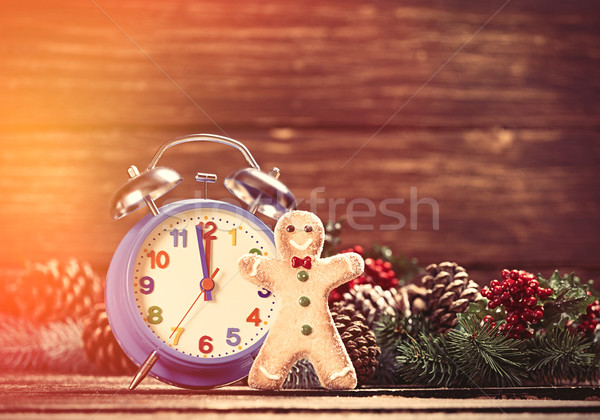 Alarm clock near Pine branches and gingerbread on wooden table. Stock photo © Massonforstock