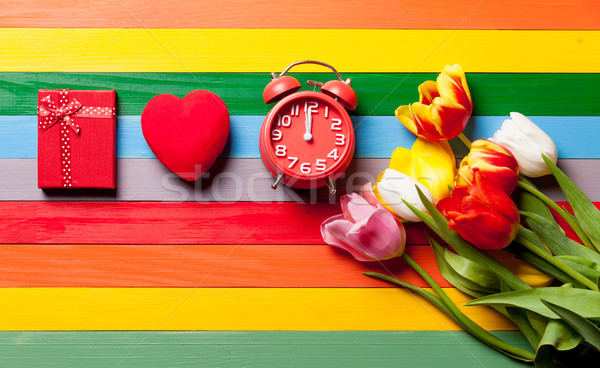 bunch of tulips, gift, heart shaped toy, alarm clock on the wond Stock photo © Massonforstock