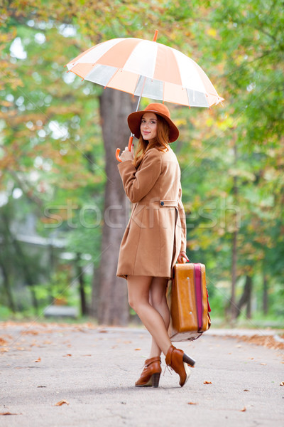 photo of beautiful young woman with suitcase and umbrella on the Stock photo © Massonforstock