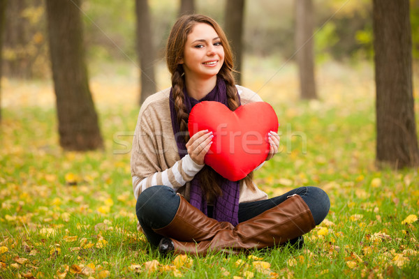 Stock photo: Girl with toy heart at autumn park.