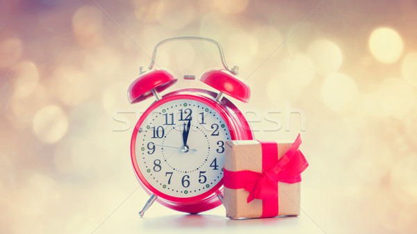 big red alarm clock and beautiful gift on the fairy lights bokeh Stock photo © Massonforstock