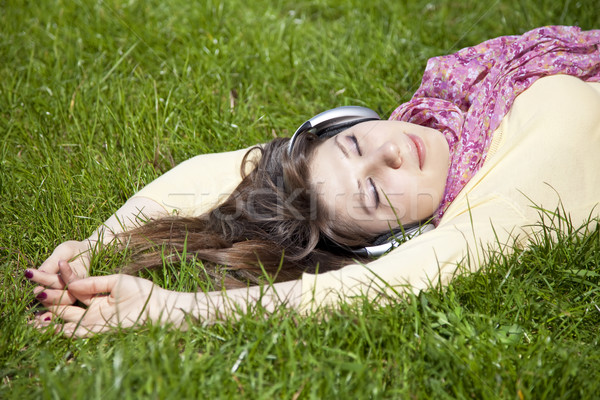 Brunette girl with headphone lies in the park. Stock photo © Massonforstock