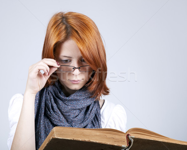 Young doubting fashion girl in glasses with old book Stock photo © Massonforstock