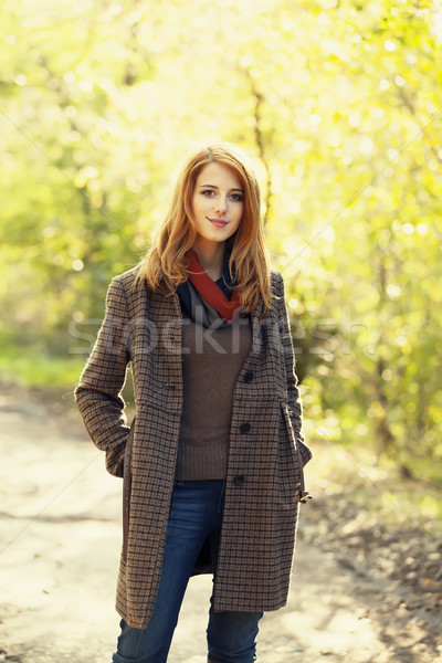 Style redhead girl at beautiful autumn alley. Stock photo © Massonforstock