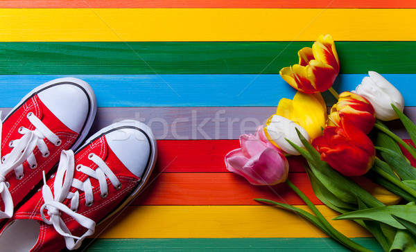 bunch of tulips, red gumshoes lying on the table Stock photo © Massonforstock