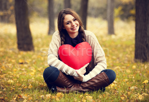 Redhead girl with toy heart at autumn park. Stock photo © Massonforstock