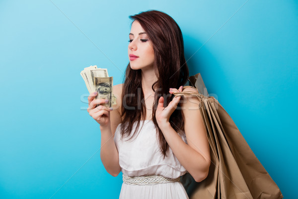 beautiful young woman with shopping bags and money standing in f Stock photo © Massonforstock