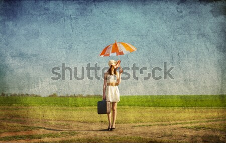Lonely girl with suitcase and umbrella at countryside field.  Stock photo © Massonforstock