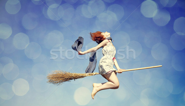 Young red-haired witch on broom flying in the sky Stock photo © Massonforstock
