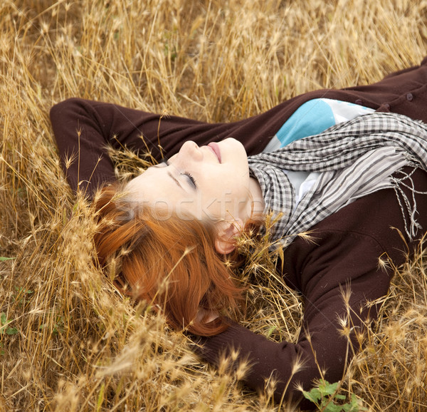 Young beautiful girl lying at yellow autumn field. Stock photo © Massonforstock