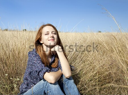Portrait of happy red-haired girl on autumn grass Stock photo © Massonforstock