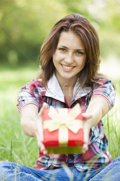 Beautiful teen girl with gift in the park at green grass. Stock photo © Massonforstock