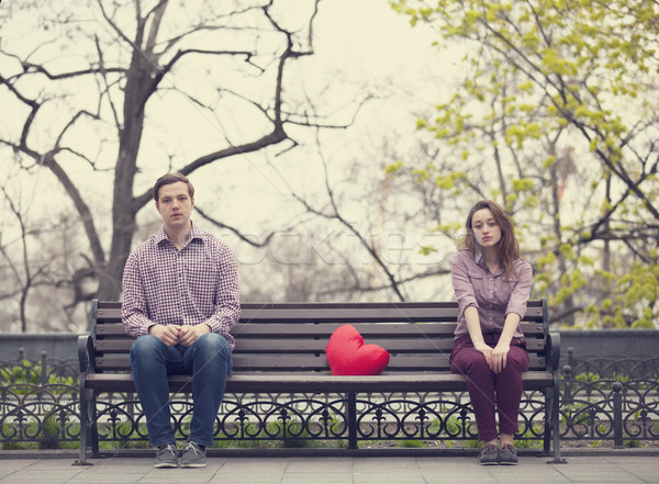 Sad teens sitting at the bench at the park Stock photo © Massonforstock