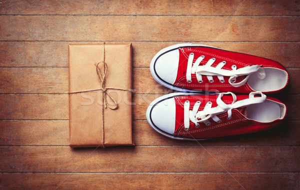 Red gumshoes and package on wooden table.  Stock photo © Massonforstock