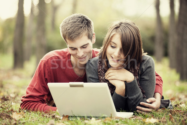 Beautiful couple with laptop at autumn park. Stock photo © Massonforstock