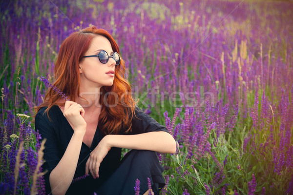 beautiful young woman sitting and relaxing on the wonderful bloo Stock photo © Massonforstock