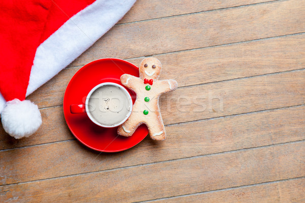 cup of coffee, gingerbread man and santa claus hat on the wonder Stock photo © Massonforstock