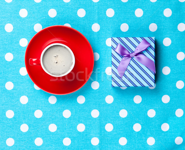 photo of cup of coffee and cute gift on the wonderful blue dotte Stock photo © Massonforstock