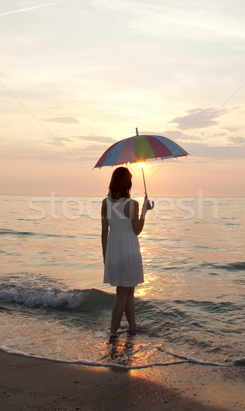 Young beautiful girl on the beach at sunrise with umbrella. Stock photo © Massonforstock