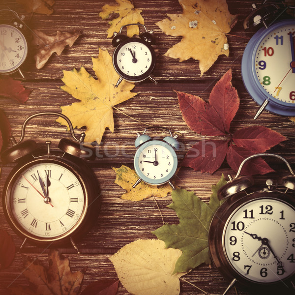Autumn leafs and alarm clock on wooden table. Stock photo © Massonforstock