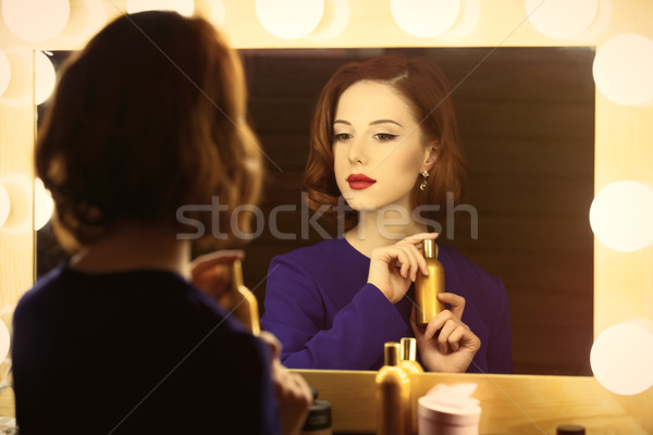 photo of beautiful young woman holding her perfume near the wind Stock photo © Massonforstock