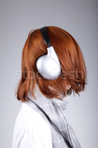 Unusual red-haired girl with headphones Stock photo © Massonforstock