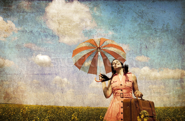 Brunette enchantress with umbrella and suitcase Stock photo © Massonforstock