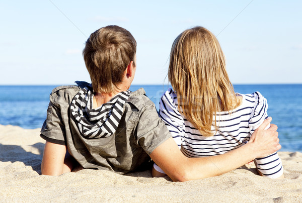happy pair of male and female on coast behind blue sea Stock photo © Massonforstock