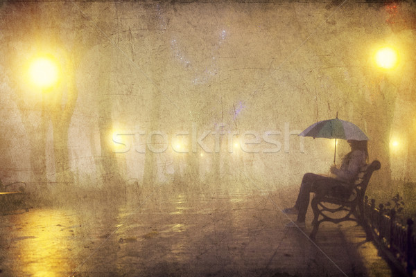 Single girl with umbrella sitting at the bench at night. Stock photo © Massonforstock