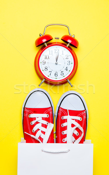 big red gumshoes in cool shopping bag and cute alarm clock on th Stock photo © Massonforstock