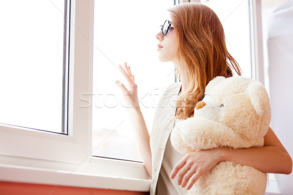 photo of beautiful young woman hugging teddy bear and standing n Stock photo © Massonforstock