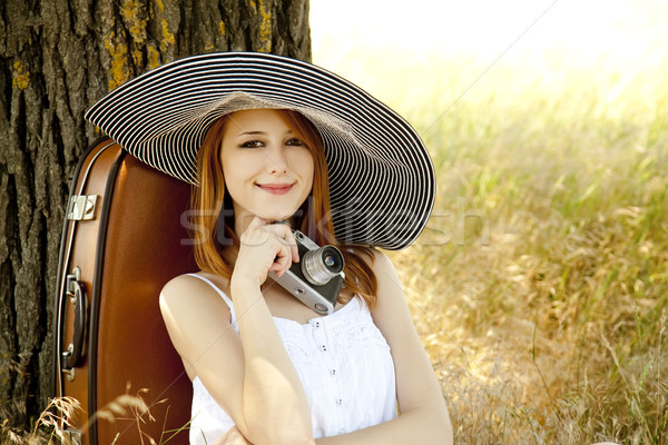 Redhead girl sitting near tree with vintage camera. Stock photo © Massonforstock