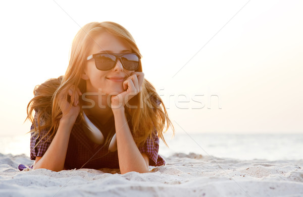 Stock photo: Red-head girl with headphones at the beach in sunrise.