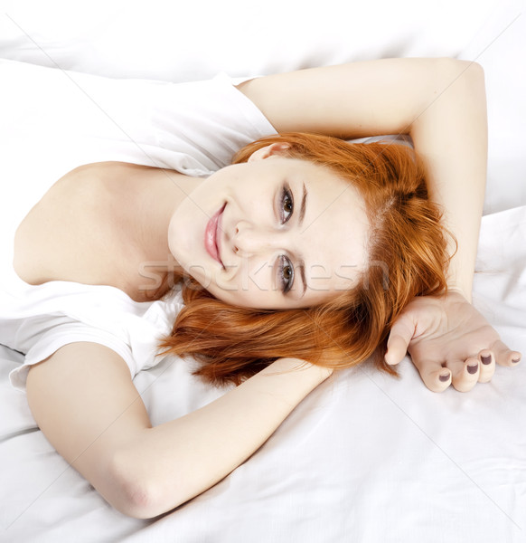 Pretty red-haired sleeping woman in white nightie lying in the b Stock photo © Massonforstock