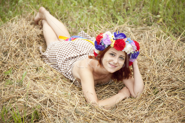 Girl in Slav national wreath lying at field. Stock photo © Massonforstock