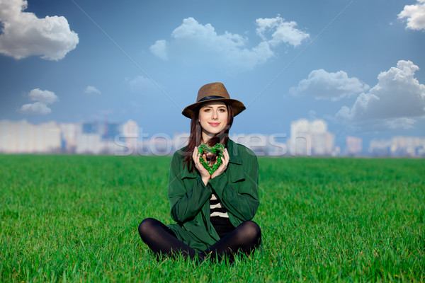 beautiful young woman sitting on the grass with heart shaped toy Stock photo © Massonforstock