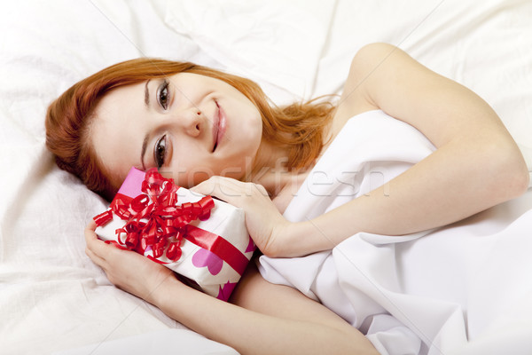 Red-haired girl in bed with gift Stock photo © Massonforstock