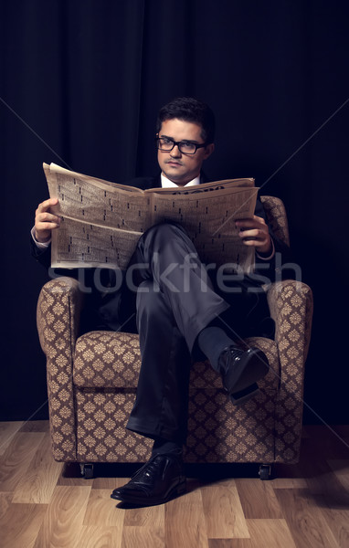 Man with cigarette and newspaper sitting in vintage armchair Stock photo © Massonforstock
