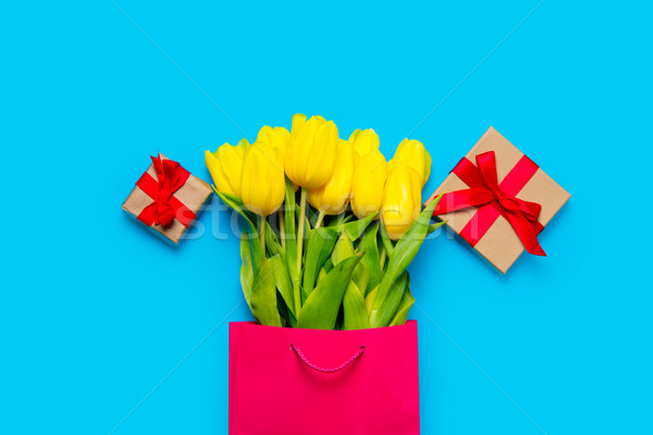 bunch of yellow tulips in cool shopping bag and cute gifts on th Stock photo © Massonforstock
