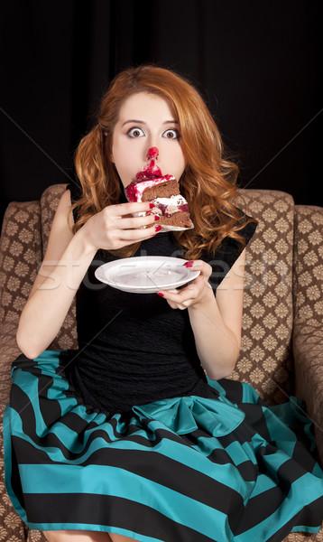 Redhead girl secretly eating cake. Stock photo © Massonforstock