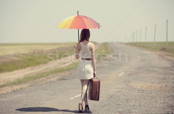 Redhead enchantress walking near rapeseed field. Photo in old im Stock photo © Massonforstock