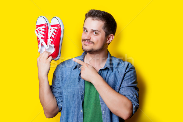 handsome young man holding red gumshoes on the wonderful yellow  Stock photo © Massonforstock