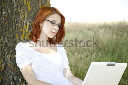 Young smiling fashion girl in glasses and notebook sitting near  Stock photo © Massonforstock