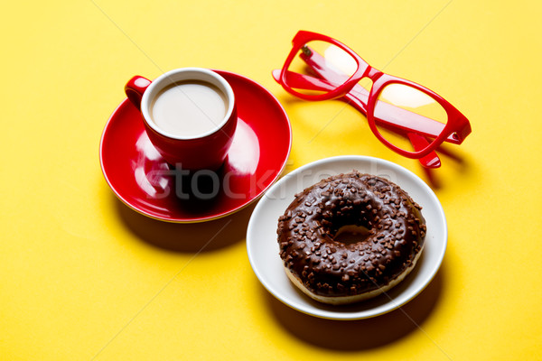 cool glasses, tasty glazed donut and cup of coffee on plates on  Stock photo © Massonforstock