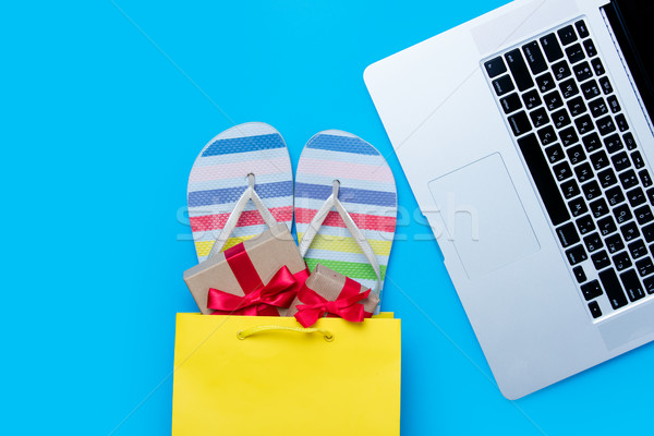 colorful sandals and gifts in shopping bag and cool laptop on th Stock photo © Massonforstock