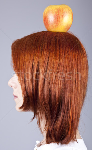 Red-haired girl keep apple on her head. Shot from sideview. Stock photo © Massonforstock