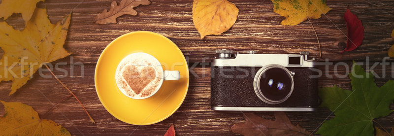 Autumn leafs, camera and coffee cup on wooden table. Stock photo © Massonforstock